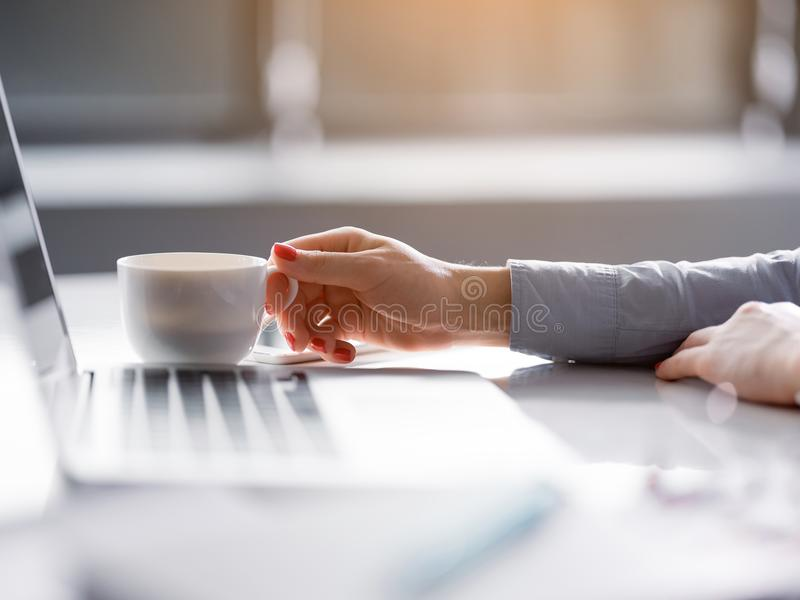 Young businesswoman drinking hot beverage near computer stock photos