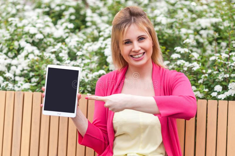 Young businesswoman in elegance style sitting in bench on park, holding tablet empty screen and pointing finger to device with. Portrait of satisfied beautiful stock photo