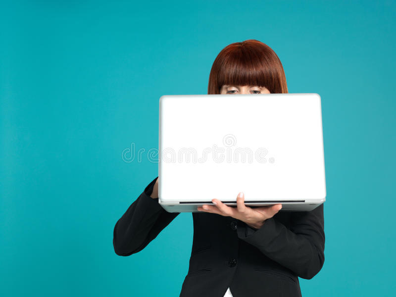 Young businesswoman, eyes showing behind laptop. Portrait of a beautiful, young businesswoman, holding a laptop in front of her, with her eyes showing, on blue royalty free stock photos