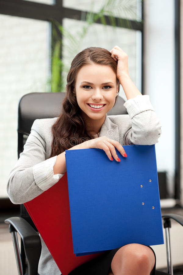 Young businesswoman with folders sitting in chair. Picture of young businesswoman with folders sitting in chair royalty free stock photos