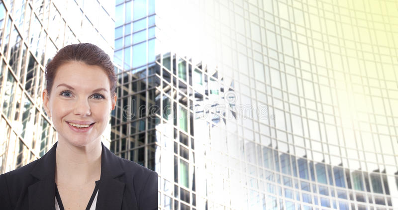 Young businesswoman in front of blurred office building background royalty free stock photo