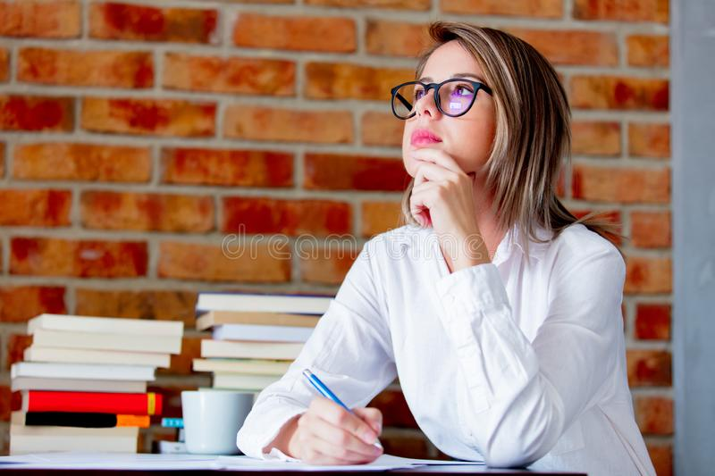 Businesswoman with pen on working place. Young businesswoman in glasses sitting on working place with pen. Brick wall on background stock image