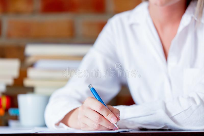 Businesswoman with pen on working place. Young businesswoman in glasses sitting on working place with pen. Brick wall on background stock photos