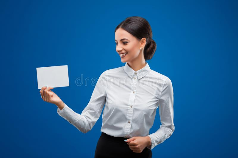 Young businesswoman happily looking at a small blank sheet of paper which shes holding to her right, isolated on blue background. Beautiful, young businesswoman stock photo