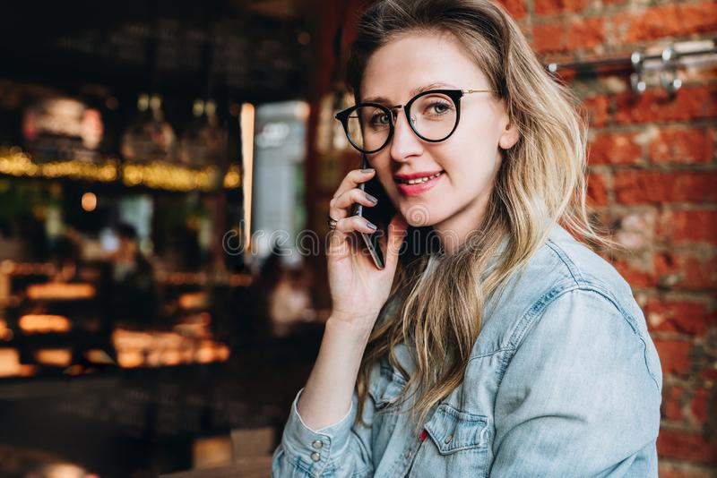 Young businesswoman has telephone conversations.Cheerful girl blogger in trendy glasses sitting in cafe,talking on phone stock image