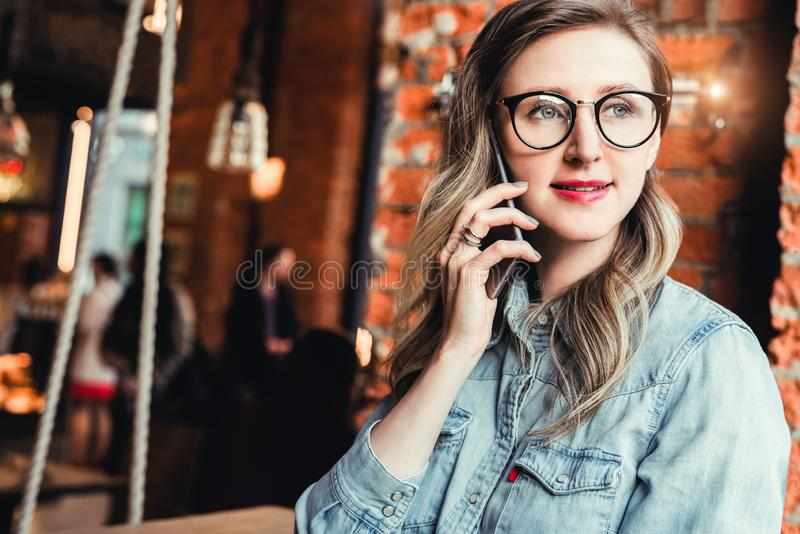 Young businesswoman has telephone conversations.Cheerful girl blogger in trendy glasses sitting in cafe,talking on phone royalty free stock image