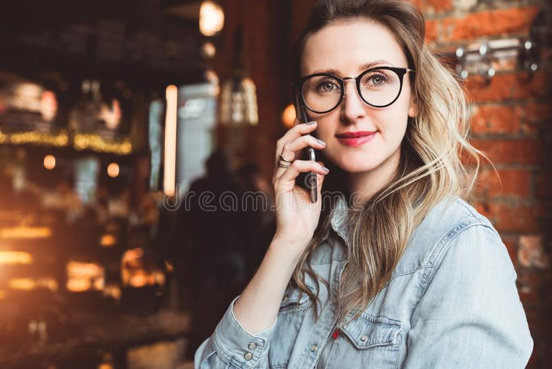 Young businesswoman has telephone conversations.Cheerful girl blogger in trendy glasses sitting in cafe,talking on phone stock photo
