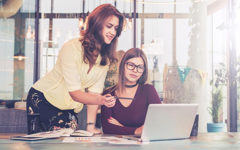 Young businesswoman helps a colleague on work. Teamwork,brainstorming. Teacher explains assignment to student. Girl is sitting in front of computer, women is stock photos