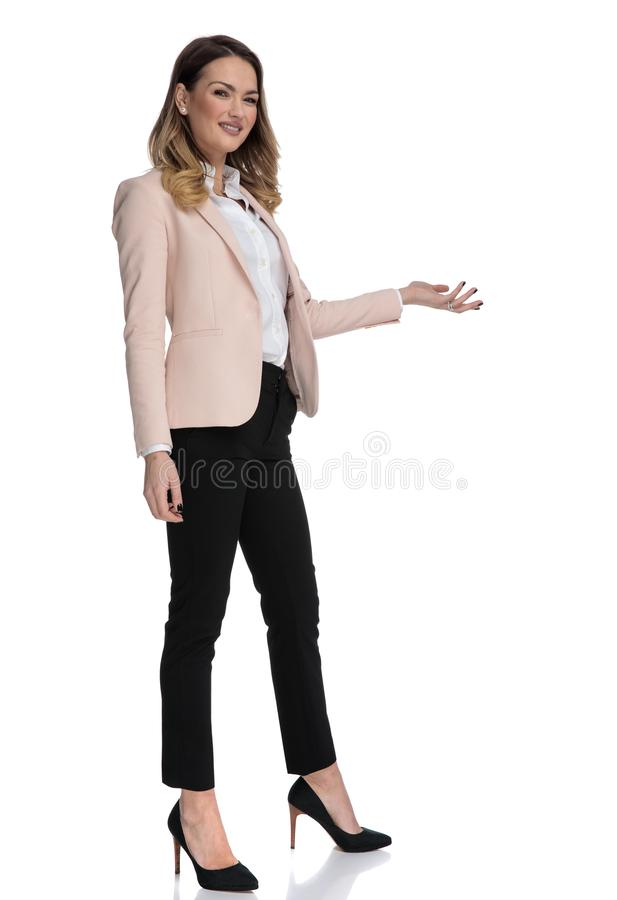 Young businesswoman in high heels presents to side stock photography