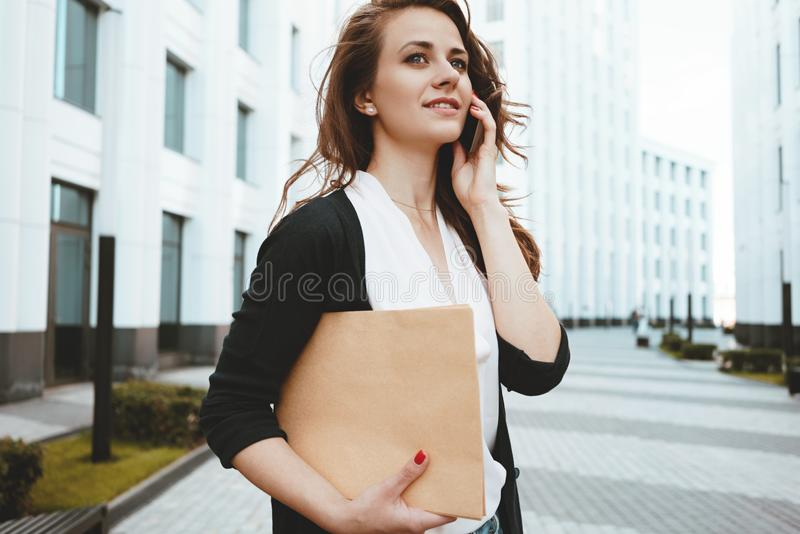 Young businesswoman hold in hand document folder and securities among urban space and talking on smartphone royalty free stock photos