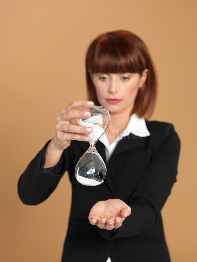 Yawning Business Woman With Hourglass On The Desk Stock