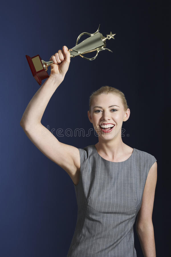 Young Businesswoman Holding Up Trophy royalty free stock photo