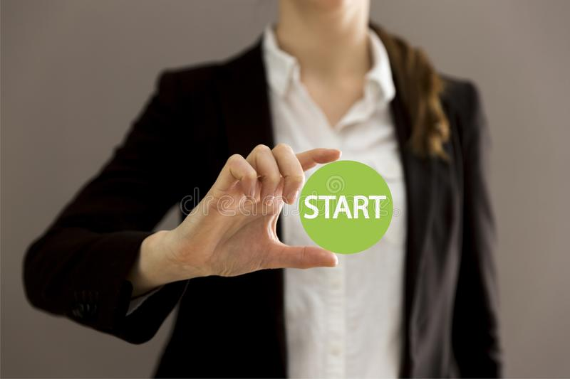 Young businesswoman holding virtual button start. New start, beginning, business concept royalty free stock images