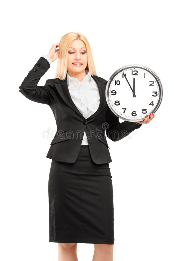 A Young Businesswoman Holding A Wall Clock In Her Hand And Gestu Stock Images