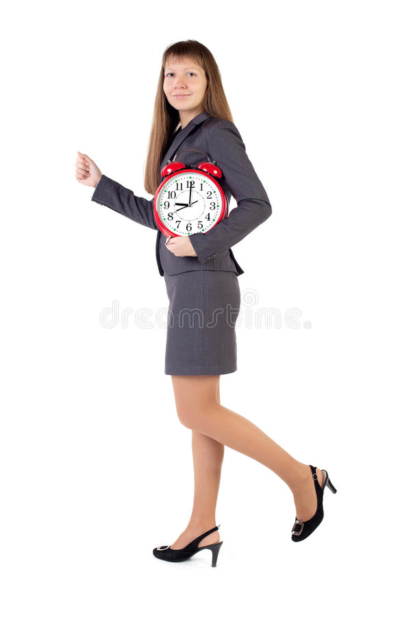 Young businesswoman holds in his hands alarm clock. Isolated white background royalty free stock image