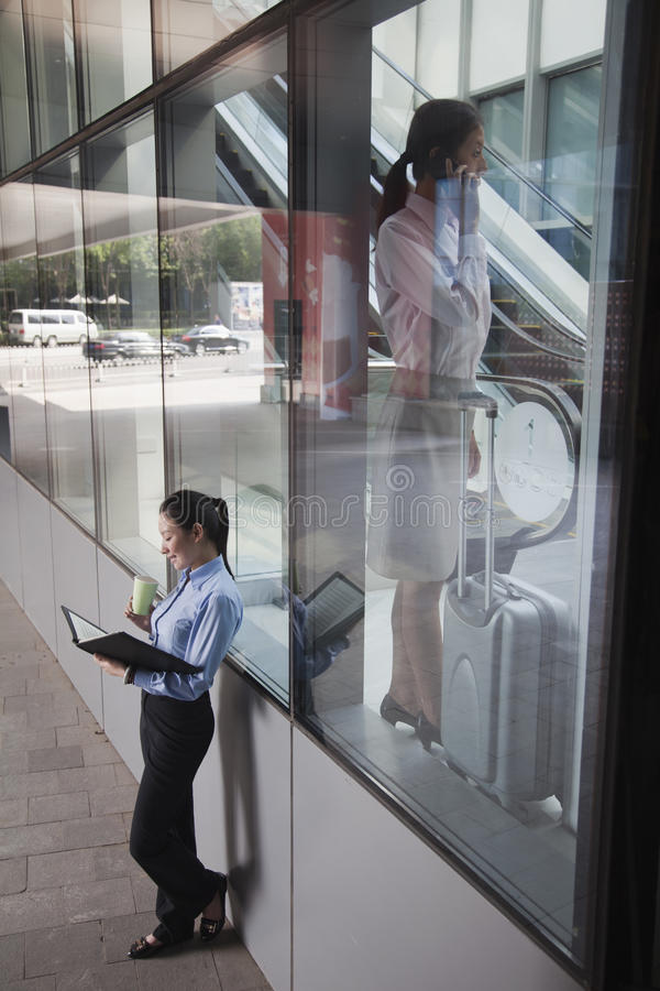 Young Businesswoman Inside The Building Talking On The Phone, Another Women Outside Of The Building Looking At Her Notes Stock Image