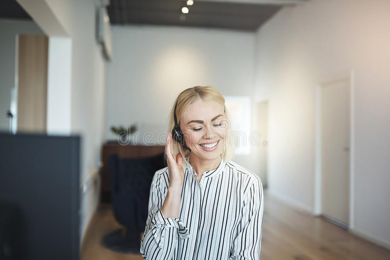 Young businesswoman laughing while talking on a headset at work royalty free stock image