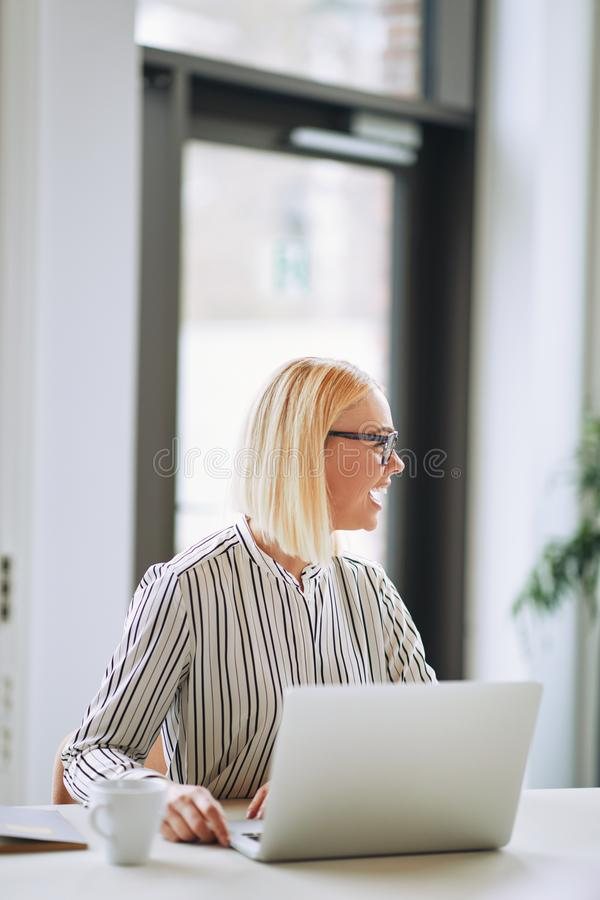 Young businesswoman laughing while working on a laptop stock photo
