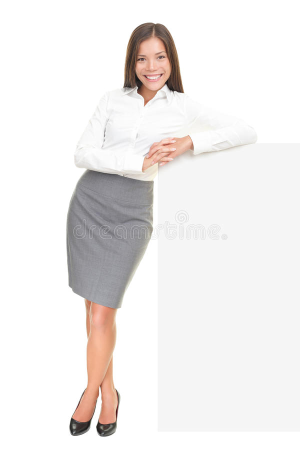 Young businesswoman leaning on sign stock photography