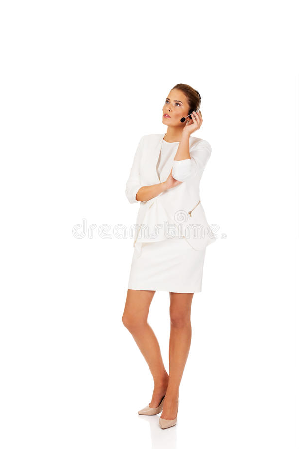 Young businesswoman listen someone at headphones royalty free stock photography
