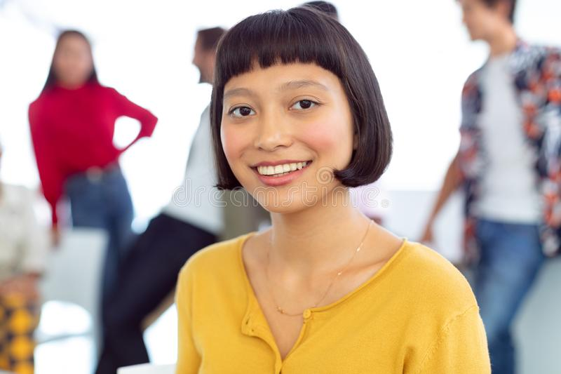 Young businesswoman looking at camera in a modern office. Front view of happy young Asian businesswoman looking at camera in a modern office royalty free stock image
