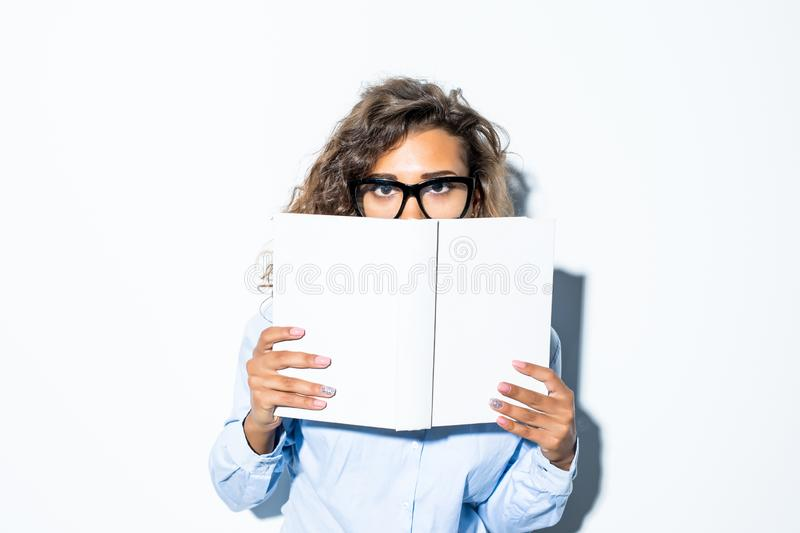 Young latin businesswoman in glasses looking over book cover isolated on white background. Young businesswoman looking over book cover isolated on white stock photography