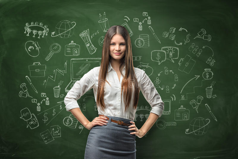 Young businesswoman looks directly at the camera and smiles on the background of the blackboard with chalk drawings royalty free stock photography