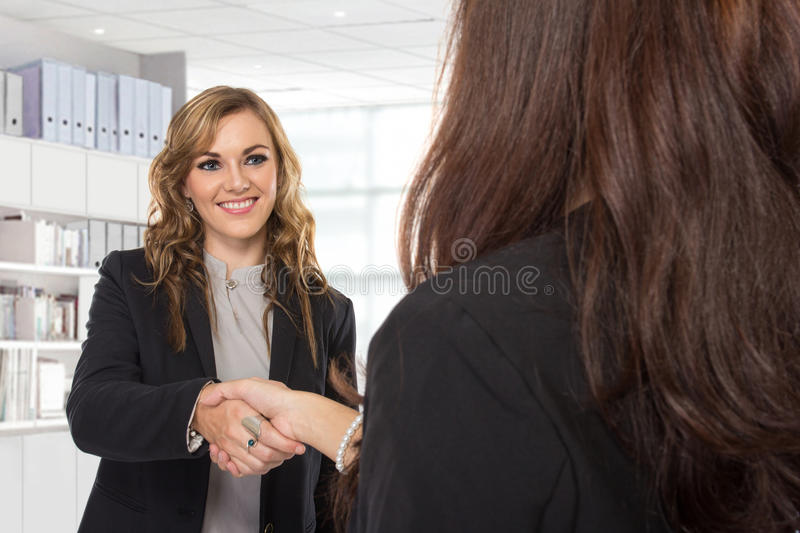 Young businesswoman making a deal. A portrait of a two young businesswoman making a deal and shaking hands in the office stock image