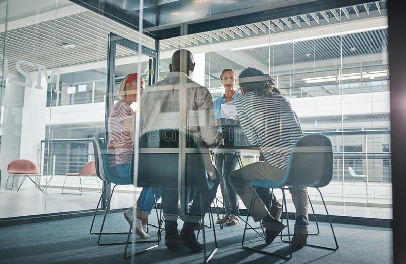 Young businesswoman meeting with her team in a boardroom royalty free stock photography