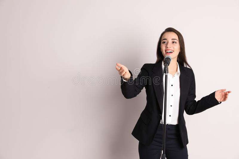 Young businesswoman with microphone on color background. stock photos