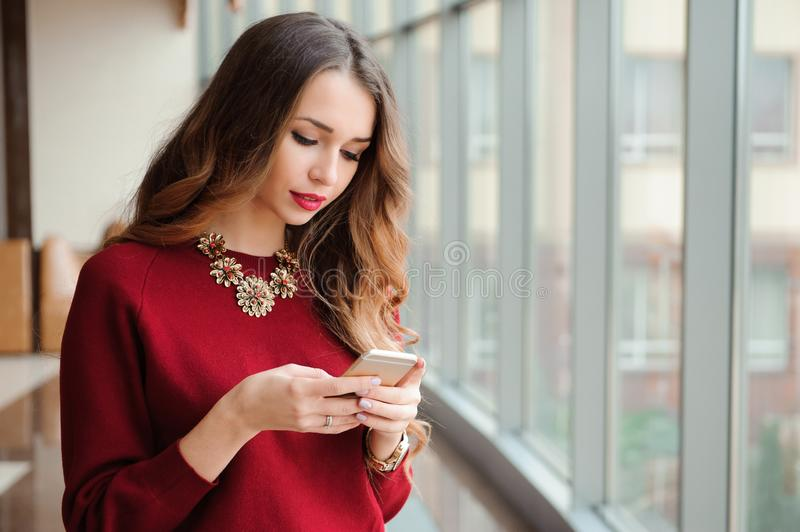 Young businesswoman with mobilephone in the office. royalty free stock image