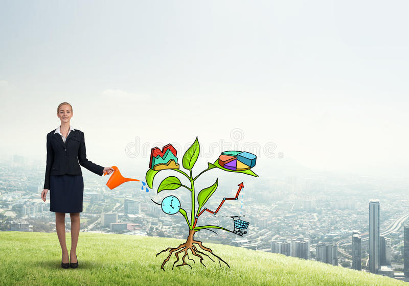 Young businesswoman outdoors watering drawn growth concept with can. Attractive businesswoman presenting investment and financial growth concept stock image