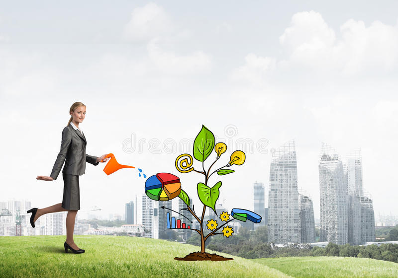 Young businesswoman outdoors watering drawn growth concept with can. Attractive businesswoman presenting investment and financial growth concept stock photos