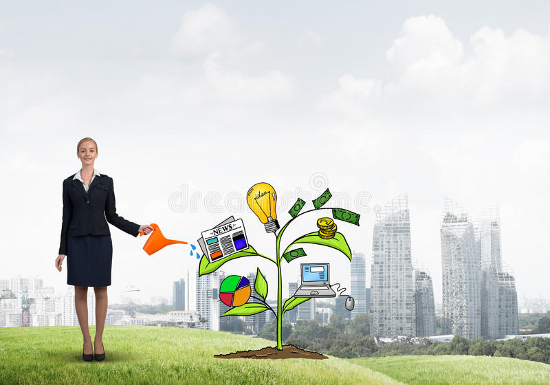 Young businesswoman outdoors watering drawn growth concept with can. Attractive businesswoman presenting investment and financial growth concept stock photo