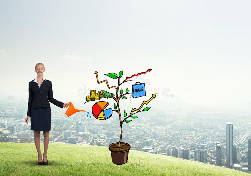 Young businesswoman outdoors watering drawn growth concept with can. Attractive businesswoman presenting investment and financial growth concept royalty free stock photo
