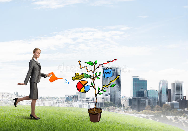 Young businesswoman outdoors watering drawn growth concept with can. Attractive businesswoman presenting investment and financial growth concept stock images