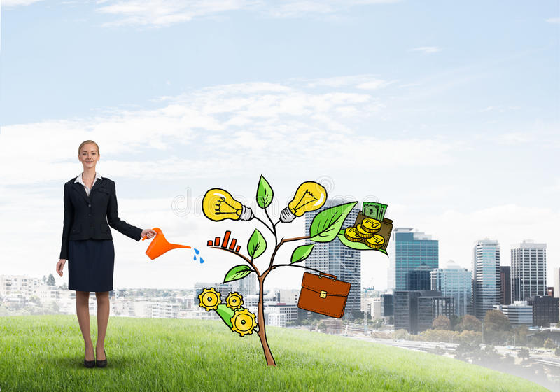 Young businesswoman outdoors watering drawn growth concept with can. Attractive businesswoman presenting investment and financial growth concept stock photography