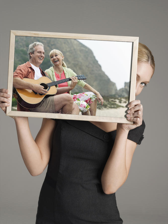 Young businesswoman peeking from behind photograph of happy couple with guitar on vacation against gray background stock photography