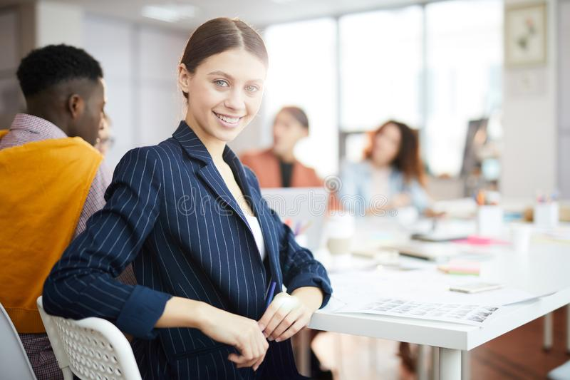 Young Businesswoman Posing. Portrait of successful young businesswoman smiling at camera while sitting at table in  business meeting, copy space royalty free stock images