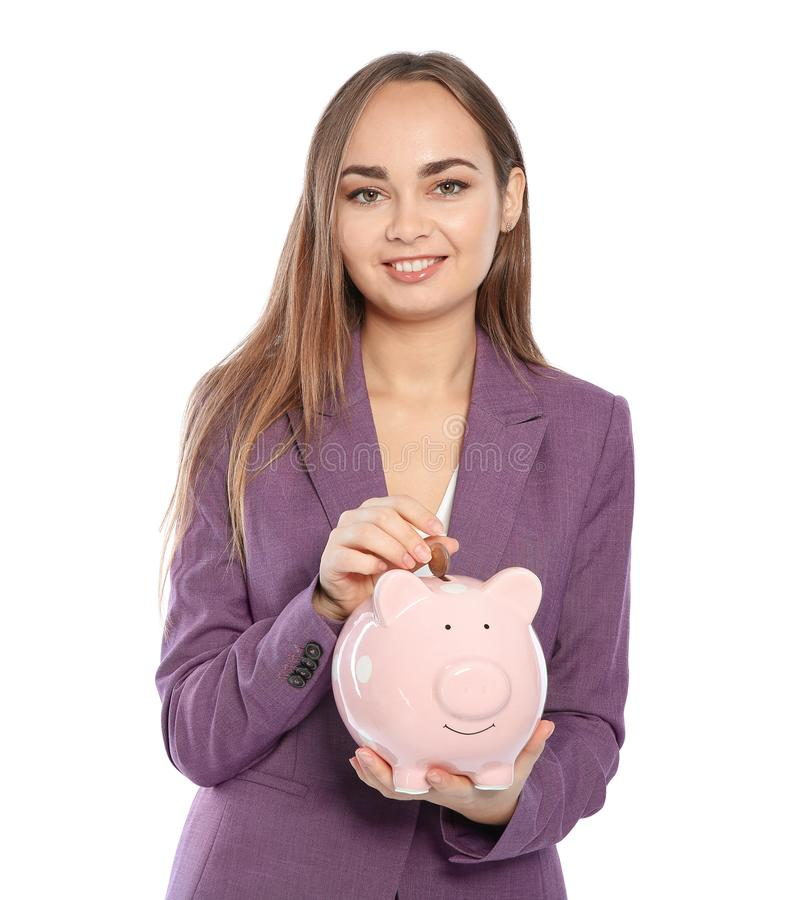 Young businesswoman putting coin into piggy bank royalty free stock image