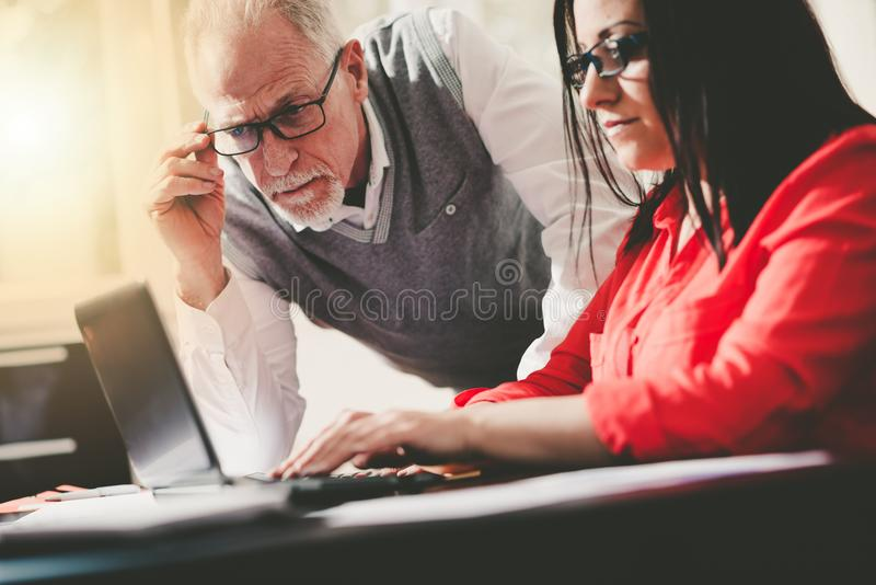 Young businesswoman and senior businessman working together, light effect stock photography