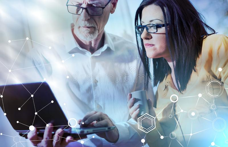 Young businesswoman and senior businessman working together; light effect royalty free stock image