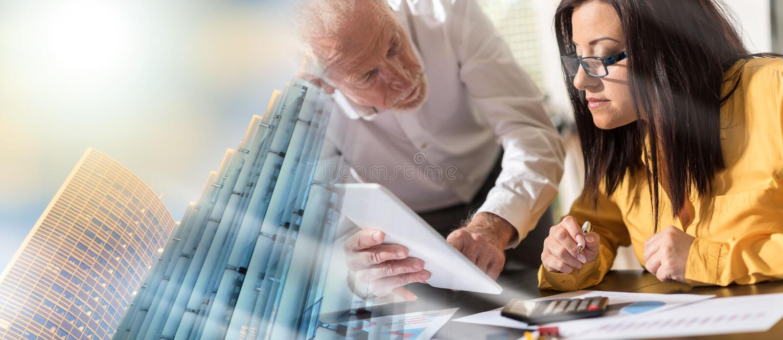 Young businesswoman and senior businessman working together; multiple exposure royalty free stock images