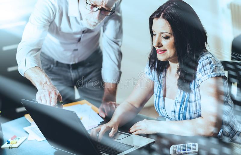 Young businesswoman and senior businessman working together, light effect; multiple exposure royalty free stock photo