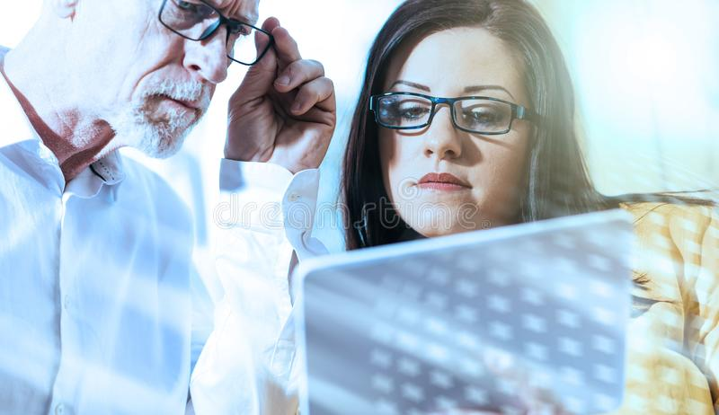 Young businesswoman and senior businessman working together; light effect stock photo