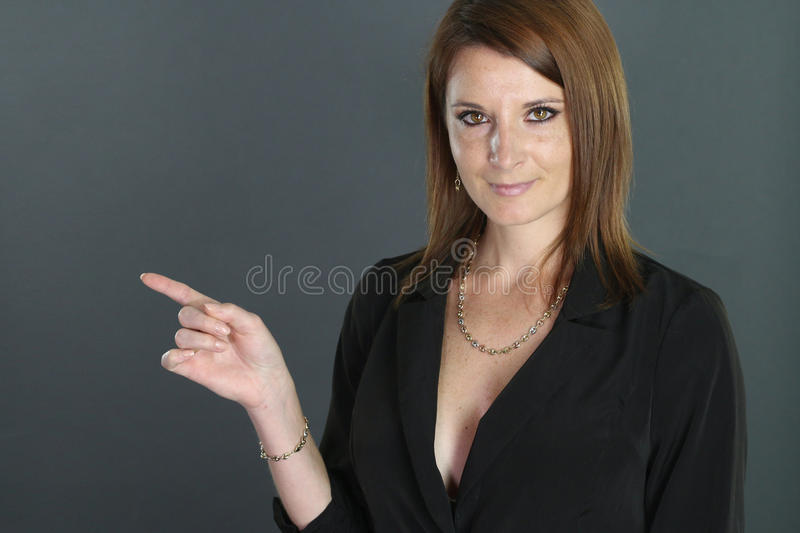 Young businesswoman showing with his finger. Over a gray background royalty free stock photography