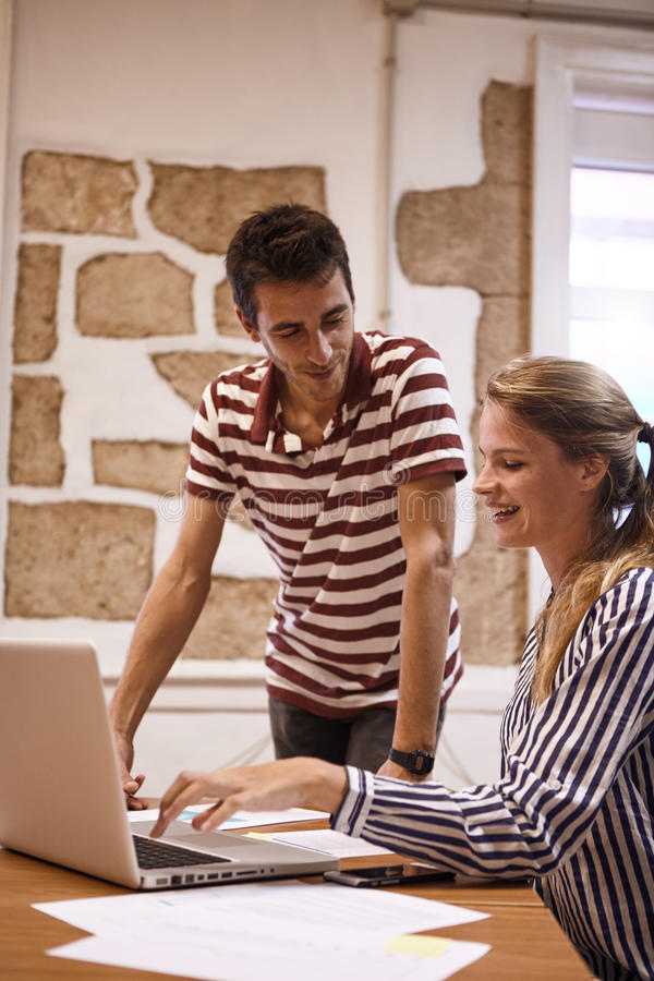 Young businesswoman showing something to man. Professional young businesswoman showing a young men something on a laptop they are sharing while he is standing stock photos