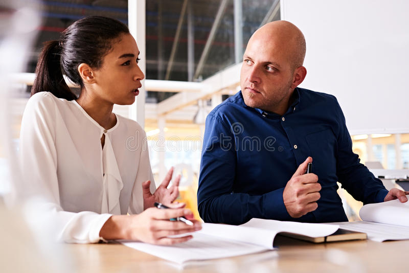 Young businesswoman showing uncertainty to her male business partner. Young business women expressing uncertainty about her caucasian male business partner's new stock photos