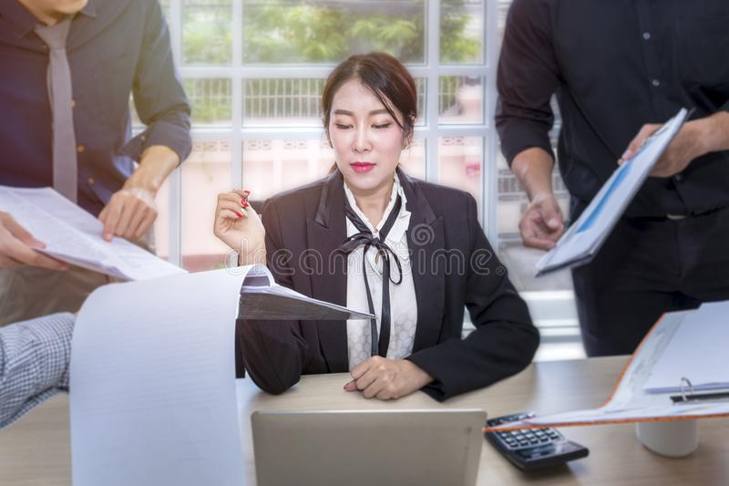 Young businesswoman sign a document and meeting with business team stock images