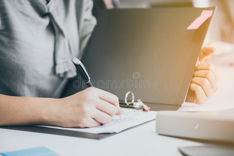Young businesswoman signs papers on a table in an office. stock photo